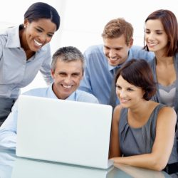 Portrait of cheerful executives looking at laptop together in office