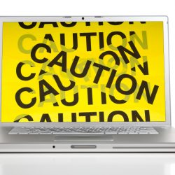 A silver computer with clipping path with caution barrier tape on the screen.  Computer security concept